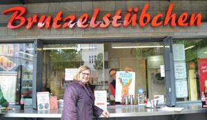 Bezirksbürgermeisterin Angelika Schöttler bei der Plakataktion vor dem Brutzelstübchen. Foto: Wirtschaftsförderung